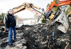 Åtta grävmaskiner jobbar för fullt vid Humlegårdsstrand just nu. Bo Haraldsson, en av de boende som engagerat sig i jätteprojektet, kikar ner på huvudledningen.
