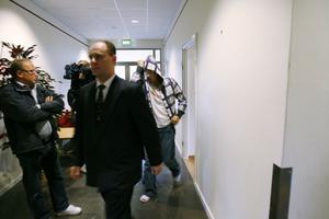 En av de misstänkta bankrånarna följer efter sin försvarsadvokat Jan Nyman in i rättsalen.