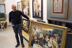 Håkan Hedin visar upp konstverket Roddarnas frukost av den franske målaren och skulptören Pierre-Auguste Renoir.
