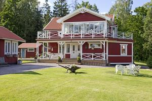 I bakgrunden vilar huset, rött med vita detaljer.