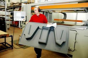 AMBULANS. De formade delarna av grå plast ska bli inredning till en ambulans. Jari Tunninen på Forma Plas i Ockelbo har just lyft en skiva ur  vakuumformaren.