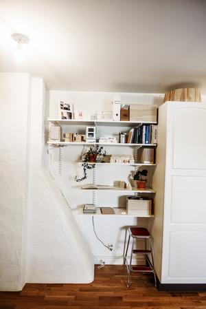 I vindsvåningen finns flera nischer. Den här har fått bli plats för en bokhylla. Ovanpå garderoben skymtar Linnéas egendesignade lampa Knall i borstad furu.