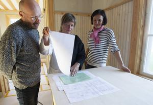 Tomas Fransson, Agneta Niklasson och Karin studerar gamla ritningar i sitt arbete med att få huset att se ut som förr.