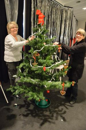 Bittan Gustavsson och Inger Broström från Kraxkompaniet hjälps åt att klä granen. Ryktet säger dock att deras arbete sker lite i onödan, då granen kommer välta under julshowen.