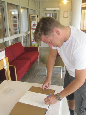 Torsten Edwinsson på Länsstyrelsen Gävleborg skriver i kondoleansboken för att visa sitt deltagande.