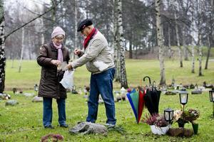 Pyntar. Jan-Erik Nyborg och Said Fransson är på Norra kyrkogården för att göra fint inför allhelgonahelgen. De har med sig ljus som ska tändas och lägger dit en krans.Foto: Lennart Lundkvist