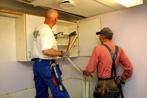 Antti Pietarila och Roger Wikner monterar ner ett skåp från väggen, som ska sparas för att eventuellt kunna sättas upp någon annan stans i centrumhuset.