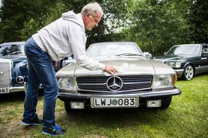 Kalle Johansson torkar bort lite regnstänk från sin Mercedes Benz 107 från 1972.
