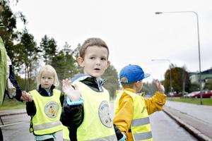 Barbro, Maja, Noah och Milo vinkar och tackar till bilarna som stannat för att släppa över dem.