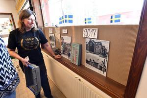 Marie Kivemäki som är butiksföreståndare i Sörsjön vid en del av de gamla bilderna som speglar 100 års affärsverksamhet i Sörsjön.