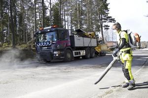 Kristoffer Dahlström kör med sandblåsare och i bakgrunden sopas sanden upp med maskin.
