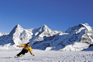 Skidåkning framför 4 000 meters-topparna Eiger, Mönch och Jungfrau.