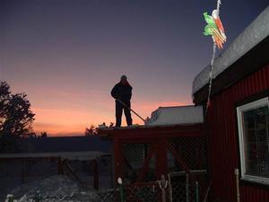 Christina skottar snö från ett hundgårdstak i Trångsviken, skriver Harriet Grabler.