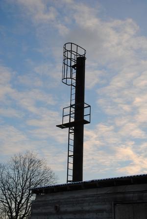 Panncentralens skorsten stäcker sig högt upp skyn.