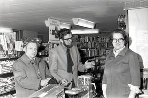 Sista kunderna. Bertil Esenius och Peter Kougi expedieras av Ingrid Eriksson på påskafton 1975. Efter det är butikens saga all.