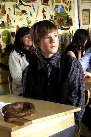 Linus Dahlberg har lagt mössan på borden och tittar mot läraren och försöker komma på svaren på hennes frågor.