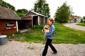 Böcker bäres in. Solveig Jonsson i byn Bittinge i Stora Mellösa socken har startat ett eget bibliotek i en lada, bredvid sitt bostadshus.