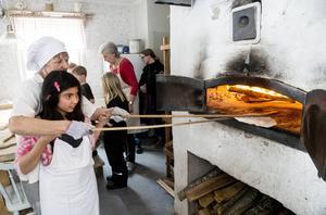 Inger Olsson hjälper Shams yassin med sitt tunnbröd.