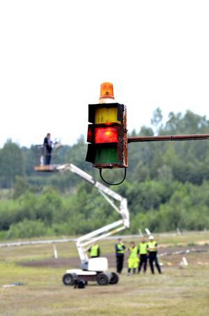Även om lampan lyser rött morrar bilarna på startlinjen och funktionärerna är redo.