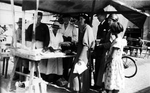 Kö till Brandts köttstånd. I mitten Ellen Brandt, omgiven av sonen Harald och maken Erik Axel. Bilden togs på Stora torget i Västerås i mitten av 1930-talet. Flickan längst fram i kön är Brandts dotter Ellen.