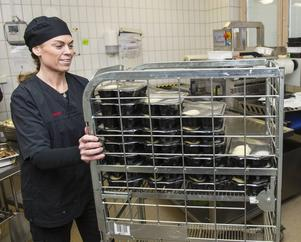 Christina Sandberg kör i väg vagnen med matlådor.