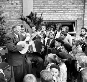 Pojkarna har basker eller mössa och flickorna prydliga hårband. Bilden är tagen någon gång på 50-talet, men var? Och vem är det som sjunger för barnen?