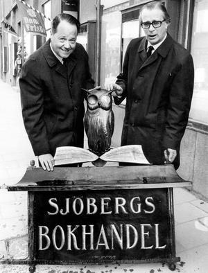 Sjöbergs tar ner skylten. Den klassiska bokhandelsskylten togs ner från Stora gatan år 1969 när Sjöbergs flyttade till Hantverkargatan. Siste ägaren Lennart Hygrell th. Gunnar Roos, tv. från Roos Skyltfabrik som en gång tillverkade skylten.