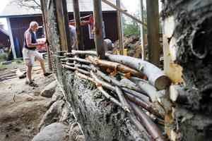 Andrew Hutchings jobbar med de flätade väggarna på fähuset. Han har rest från Uppsala för att gå kursen i lerbygge i Järbo.