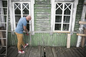 Med hjälp av en skruvdragare låser Andreas Åström dörren till kallbadhuset.