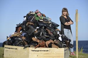 Kristina Wicksell från stiftelsen Make Equal vid manifestationen i form av en remake av Stanislaw Muchas bild på skor tillhörande de som mördades i Auschwitz-Birkenau 1940-1945. Foto: Janerik Henriksson/TT