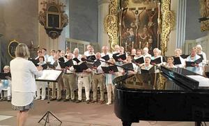 Anette Sund dirigerar Tuna-Torsångskören vid pingstaftonens konsert i kyrkan.