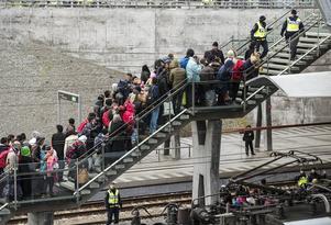 Polis övervakar kön av ankommande flyktingar i snålblåsten vid Hyllie station utanför Malmö.