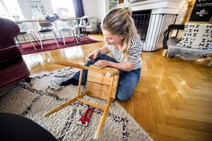 En lackad pall med sits i fuskläder får ett nytt utseende när Jennie slipar benen och sätter dit ett William Morris-tyg som har varit kappa på en fåtölj. I bakgrunden syns den soffa som hon skapat från en gammal drosksits hon hittade i en ladugård.