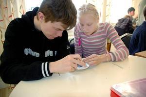 Koncentrerat. Emil Lindgren och Johanna Rauma är båda 18 år. Under måndagen hjälptes de åt att göra pärlsmycken. Det resulterade i ett halsband och ett armband.