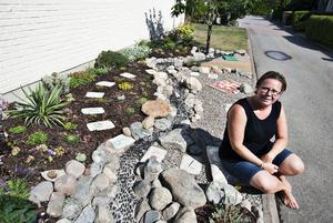 """Landskap i söderläge.   Mellan husgaveln och """"flod-bädden"""" ligger plattor med siffror, delar av soluret  som Jenny Hultin har gjort till en del av trädgårdsanläggningen. Till höger i bild, bakom Jenny, syns mattan av färgglada stenar och kudden i betong. Foto: Tony Persson"""