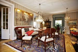 I stora salen står en Karl Johan-grupp på den senaste av de inköpta äkta mattorna. På väggen en tavla som Liz-Beth köpte på auktion efter talmannen Henry Allard.