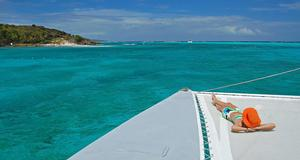 Testa digital detox på Grenadinerna. Här njuter en kvinna av livet på en båt.