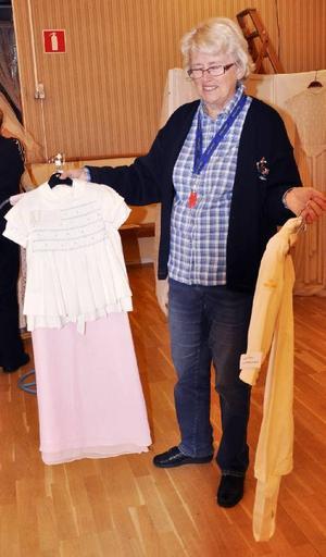 Här finns inte bara brudklänningar. Ulla Jacobsson från Hammerdals Konstförening visar ett knippe brudnäbbskläder.