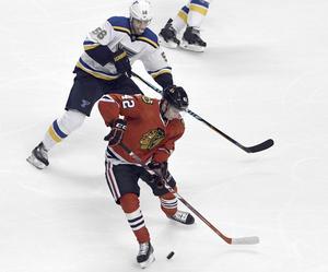 Chicagos back Gustav Forsling (röd tröja) hyllas inför NHL-premiären, här i kamp med Magnus Pääjärvi, St Louis, under en träningsmatch.