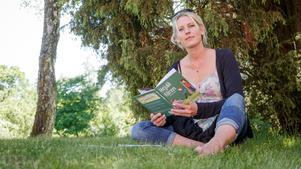 """Illustratören och författaren Johanna Sandberg med sin senaste bok """"Hejdå fåren"""" i handen."""