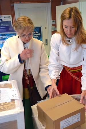 Ett spännande ögonblick när Mejt och Susanne iklädda folkdräkter från Sollerön öppnar lådan med de nya böckerna på Konsum vid Sollerön.