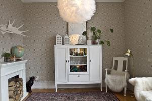 Balettlampa i egen design och skåp med samling av färgat glas, på väggen en tapet från Duros gammalsvenska kollektion.