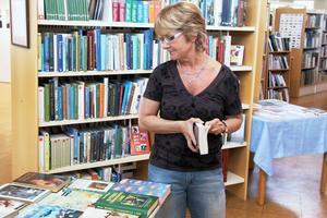 Åsa Stenberg, som jobbar på biblioteket i Edsbyn, kollar bokbytarbordets utbud av bytesböcker.