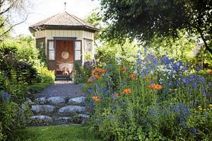 Brandliljor, iris och praktveronika blommar framför lusthuset.