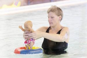 Babysiminstruktören Åsa Klockerud har jobbat i vattnet i 18 år. För att visa föräldrarna hur de ska göra använder hon bland annat en docka.