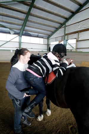Det är knepigt att ta sig upp på ryggen. Petra Sjögren hjälper Layoldi upp i sadeln på hästen Max