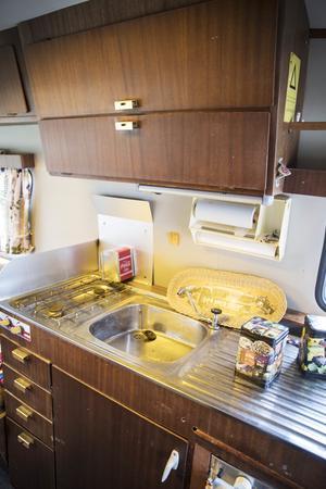 Köket är litet men klassiskt med luckor i mahogny och handtag i mässing.