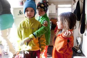I hallen. Helmi, Ivan och Bonnie Nikula klär på sig.