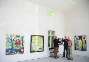 Vernissage i Färila konsthall. Konstnären står till vänster tillsammans med besökare.