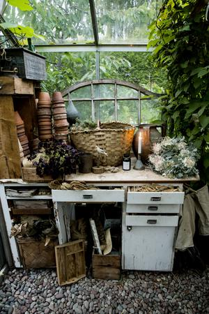 En dekorativ arbetsbänk i växthuset rymmer krukor, band poch snören som är bra att ha till hands för floristen Linda.